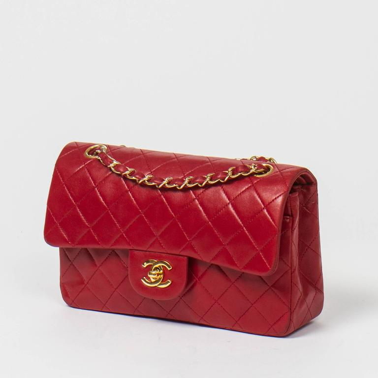 "Classic Double Flap 23cm in red quilted lambskin with double chain strap interlaced with leather, signature turnlock, gold tone hardware. Back slip pocket. Red leather lined interior with 3 slip pockets. Gold tone heat stamps ""Chanel"" "" Made in"