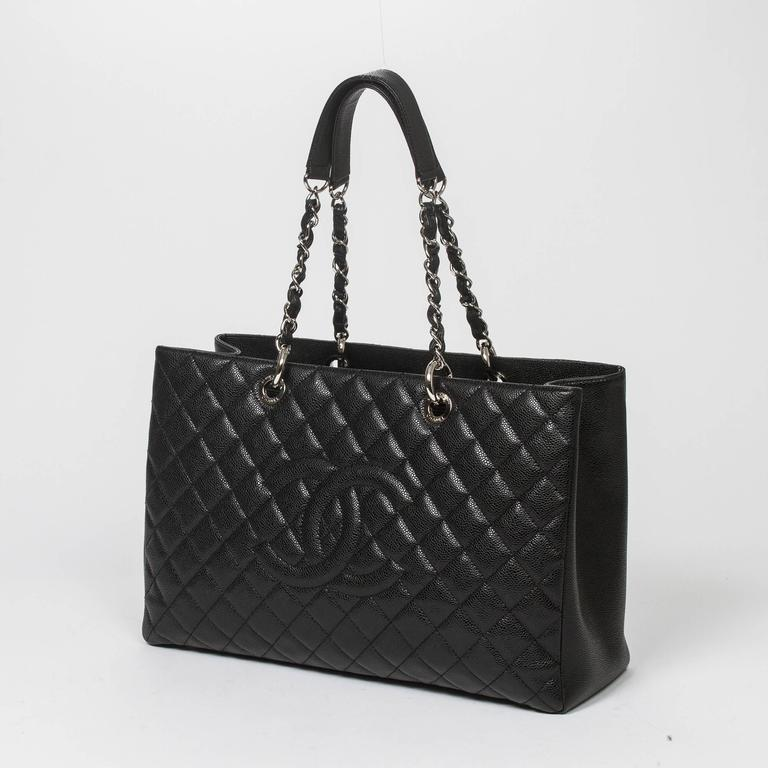 Grand Shopping Tote XL in black quilted caviar leather with chain and leather straps, silver tone hardware. Back slip pocket. 4 protective metal feet at the base. Black satin lined interior with one zipped middle compartment, 2 slip pockets and one