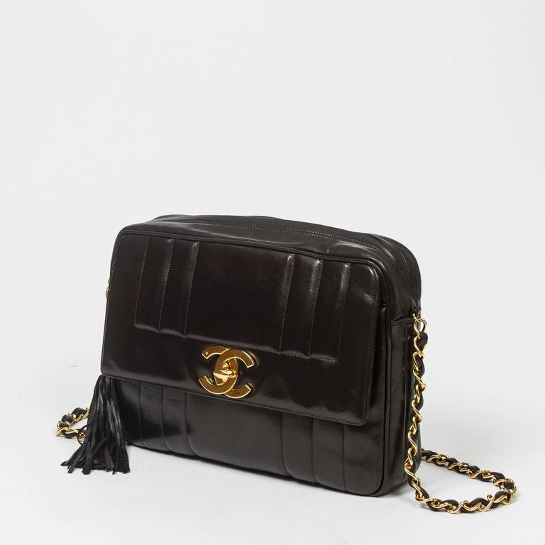 Vintage Shoulder bag in black vertical quilted lambskin, front pocket with large CC turnlock closure, chain strap interlaced with leather, gold tone hardware. Zip closure with leather tassel zipper toggle. Black leather lined interior with one slip
