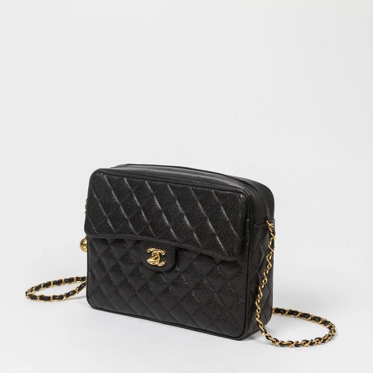 "Vintage shoulder bag in black caviar quilted leather, one large front pocket with gold tone signature turnlock. Top zipper closure with gold tone sphere zipper toggle. Black leather lined interior with one zip pocket and one slip pocket. ""CHANEL"""