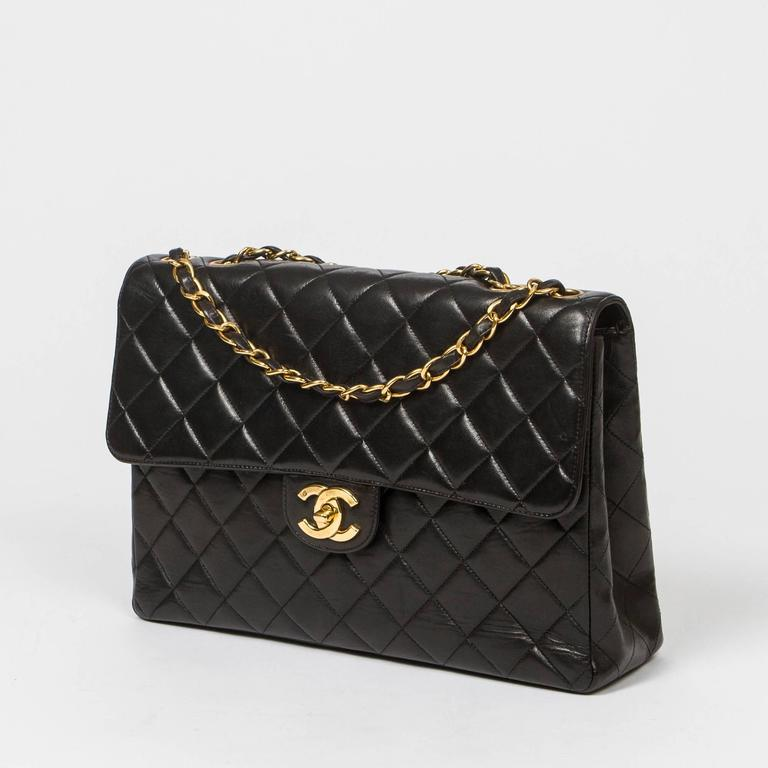 Jumbo in black quilted lambskin with double chain strap interlaced with black leather, signature CC turnlock, gold tone hardware.  Back slip pocket. Burgundy leather lined interior with one slip pocket and one zip pocket. Gold tone heat stamp