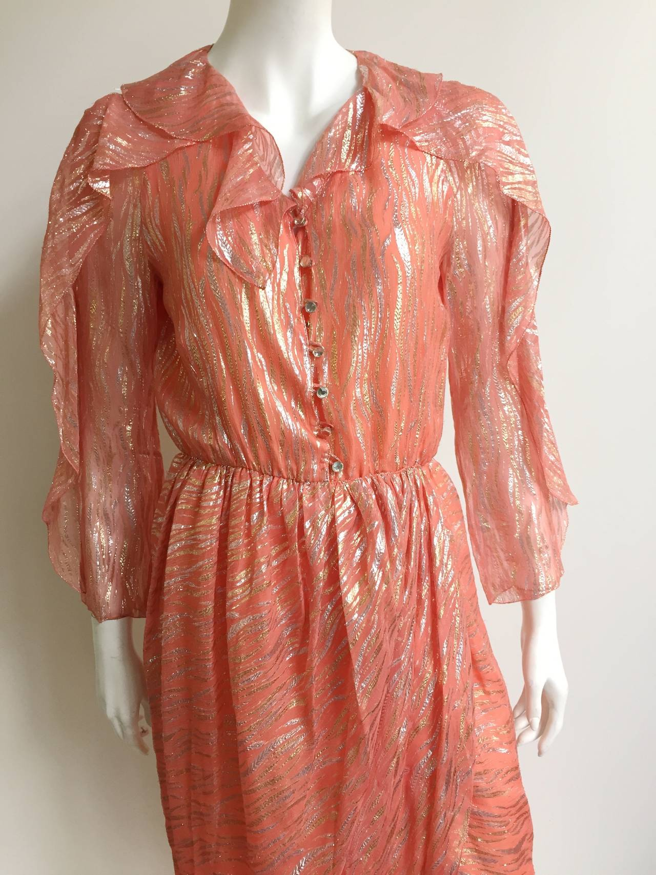 Stephen Burrows 1980s coral lame zebra print wrap dress is a vintage size 10 but fits like a modern size 6 ( please see & use measurements).  Snap button and hook on size of waist. Flowing sleeves and collar make this a very dramatic dress.