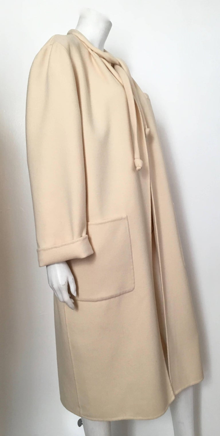 Salvatore Ferragamo for Neiman Marcus cream wool cocoon coat with large front pockets and tie string is a size 10. This absolutely stunning cream Ferragamo cocoon coat is just what the red carpet ordered. Stylish and forever chic this coat will have