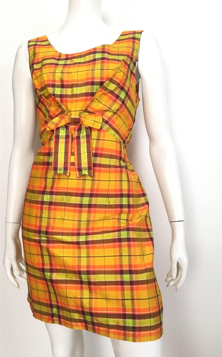 """Moschino Jeans 1990 silk plaid sleeveless dress with front bow is labeled a USA size 12 but fits more like a size 10.  The waist on this dress is 31.1/2"""" so please grab your tape measure so that you can measure your bust, waist & hips to"""