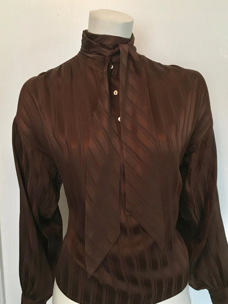 Yves Saint Laurent Rive Gauche1970s brown silk blouse with tie is a size large.  This blouse was designed to be overflowing and blousy and will fit sizes 6, 8, 10 but you be the judge of that. Classic striped pattern with tie, this blouse will have
