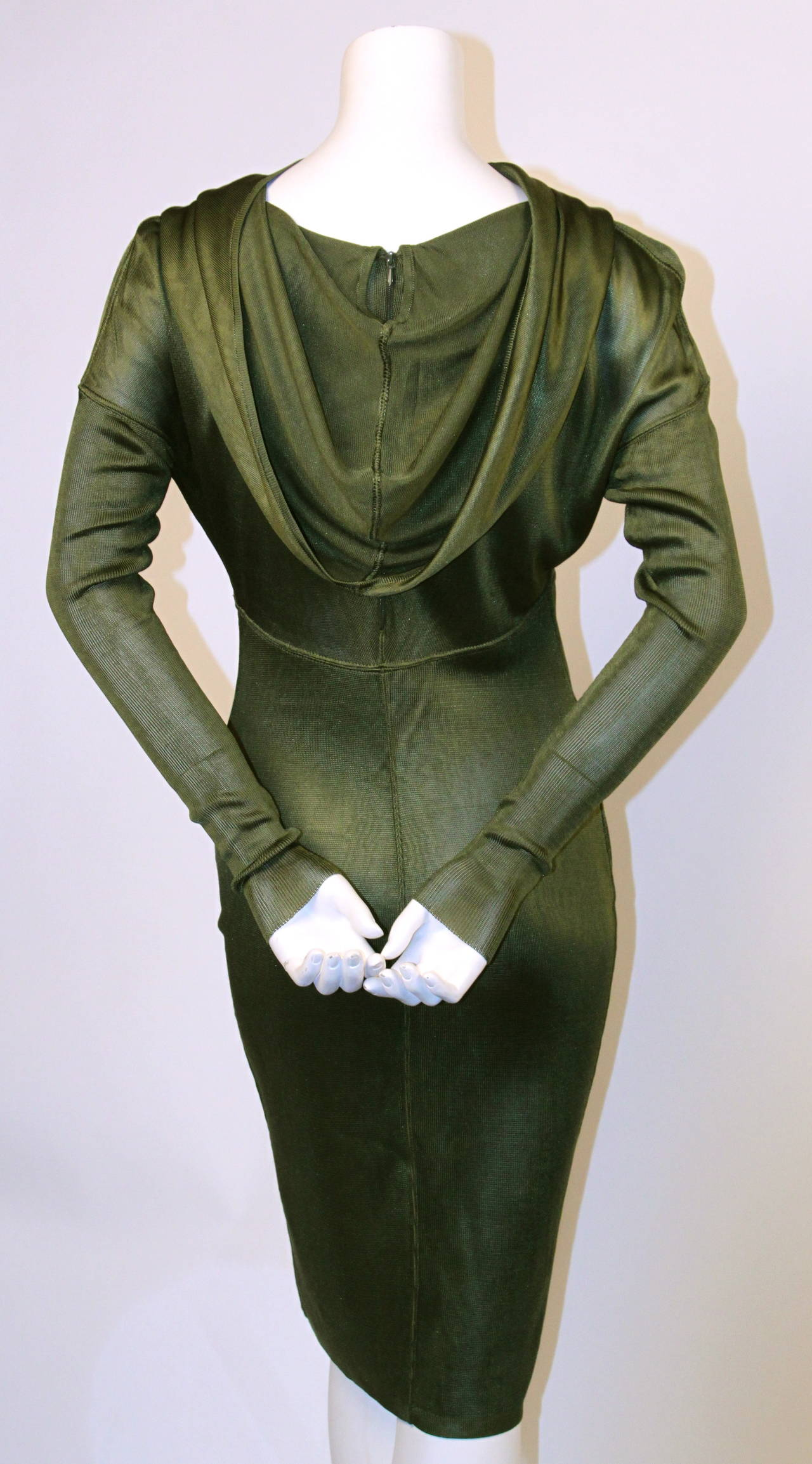 Very rare olive green hooded dress from Azzedine Alaia dating to 1986. 'Hood' can be draped for a more conventional look. Arms are made of a contrasting ribbed wool and are very long and narrow. Best suited for a size small or medium. Approximate