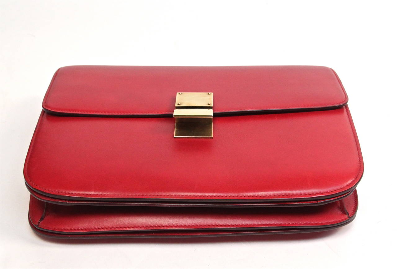 Supple, smooth red leather bag with antiqued brasstone hardware designed by Phoebe Philo for Celine Spring 2012. Bag has a fold-over front flap with push lock closure. Bag measures approximately 11.5'' at widest x 9'' tall at center x 3'' deep and