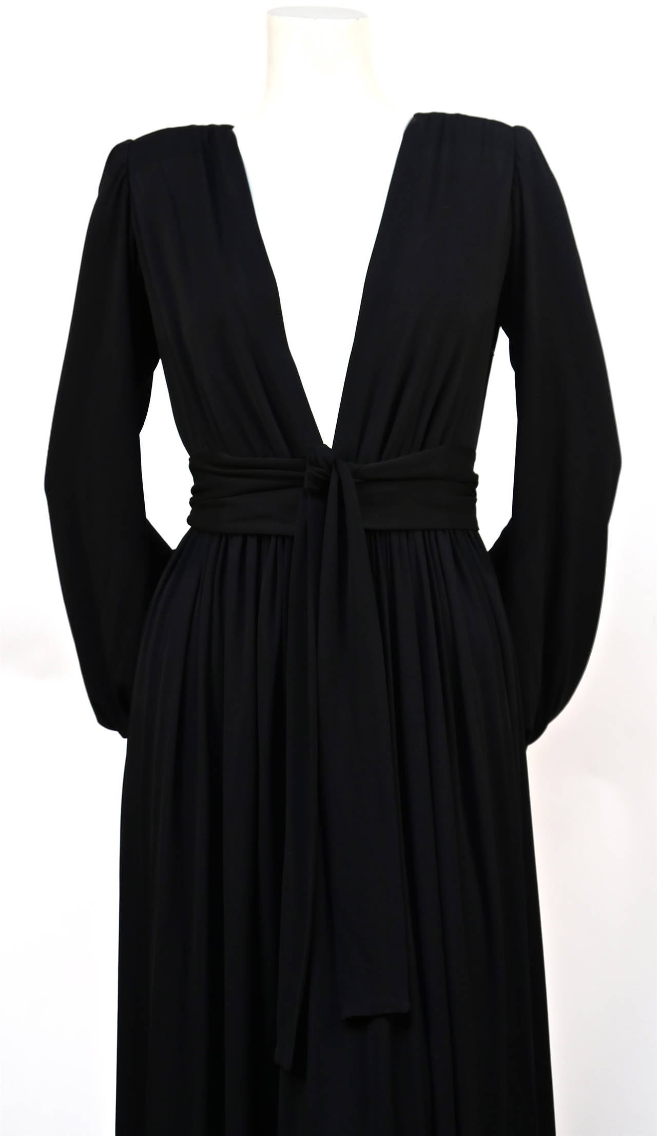"Exceptional jet black jersey gown with deep V neckline, billowy sleeves and wrap belt from Yves Saint Laurent dating to the late 1970's. Labeled a French size 36"". Approximate measurements: shoulders 14"", bust 32-33"", waist 24"", arm length 28"" and"