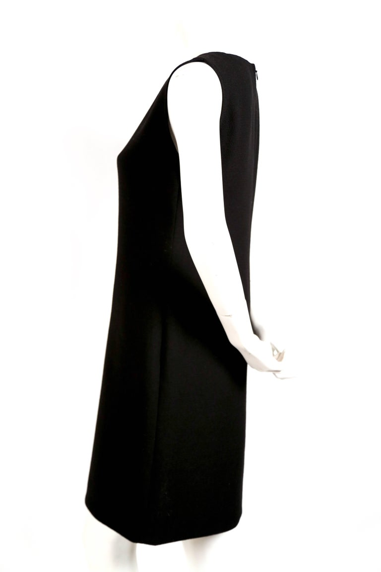 "Black wool haute couture dress with circular cut outs backed in red wool, designed by Pierre Cardin. Approximate measurements: bust 34"", waist 32"", hips 38"" and length from center back to hem 35"". Hidden back zipper. Made in"