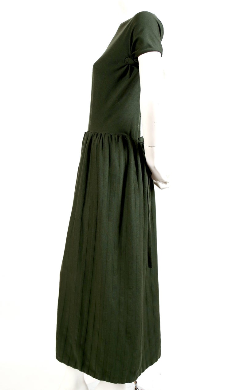 """Unusual forest green wool knit dress with long skirt and open back from Azzedine Alaia dating to the 1990's. Labeled a French size S however there is some flexibility with the sizing due to stretchy knit. Approximately 52"""" in length.  Drawstring is"""