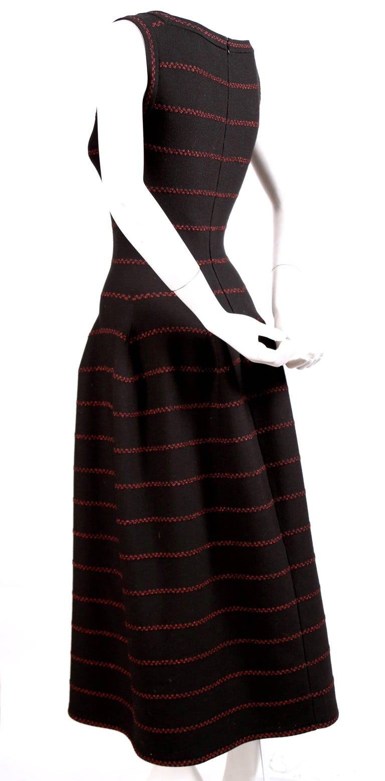 Long black knit dress with red lurex detail designed by Azzedine Alaia. Square boat neckline. Beautiful seaming creates the full skit. French size 40 which fits a US 4-6. Approximate measurements (unstretched): shoulder 14