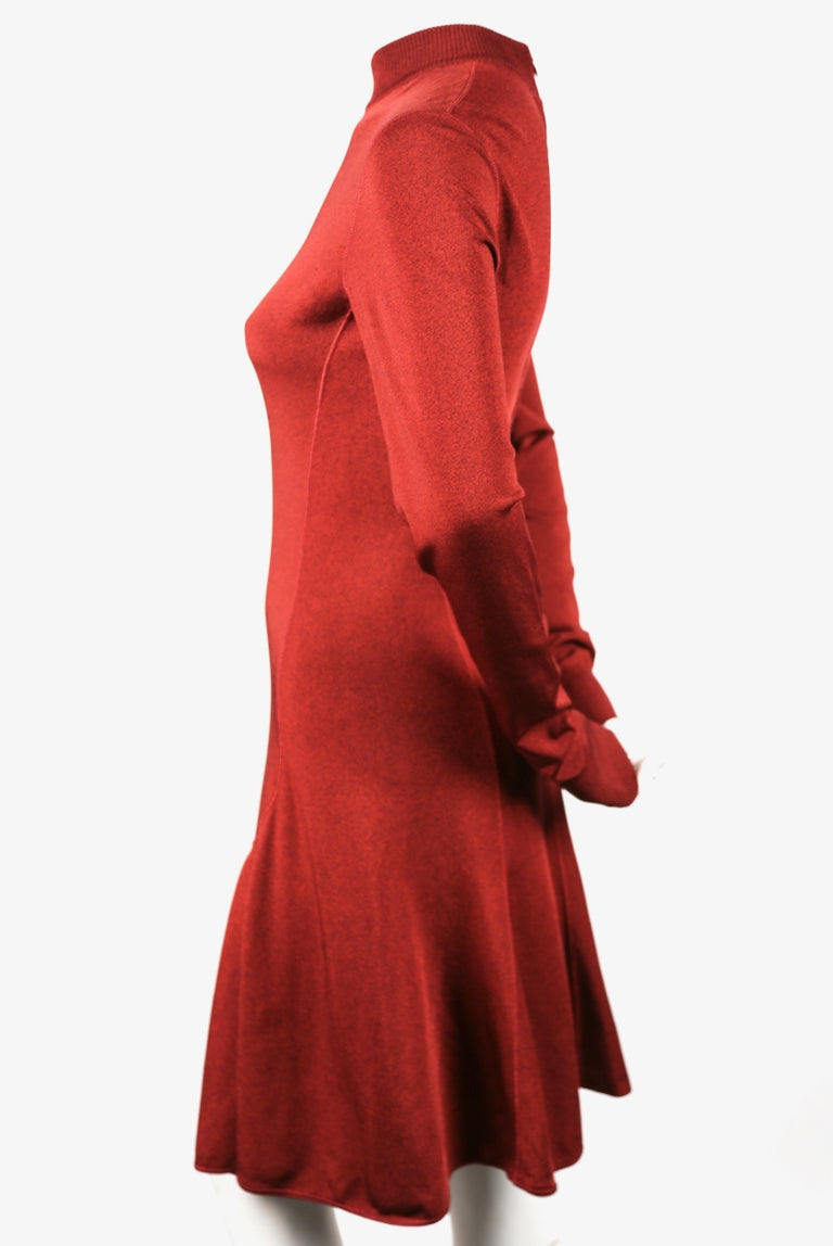Dark red flared dress with high neckline and long sleeves designed by Azzedine Alaia dating to the early 1990's. No size indicated best fits a S or M. Approximate measurements (unstretched): shoulder 15