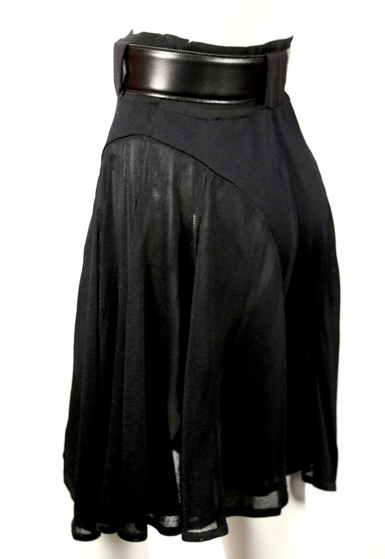 Jet black pointelle knit skort with sheer panels from Azzedine Alaia dating to the 1990's. Size XS. Approximate measurements: waist 22
