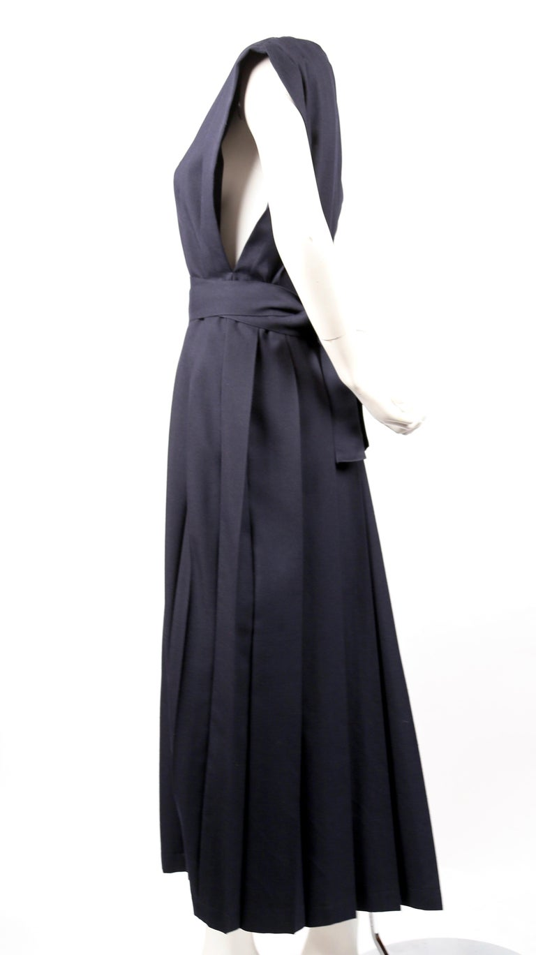 Very rare, navy-blue wool dress with box pleats and long waist tie designed by Rei Kawakubo dating to fall of 1996. No size indicated. Best fits a S or M. Width is adjustable. Approximate length 52
