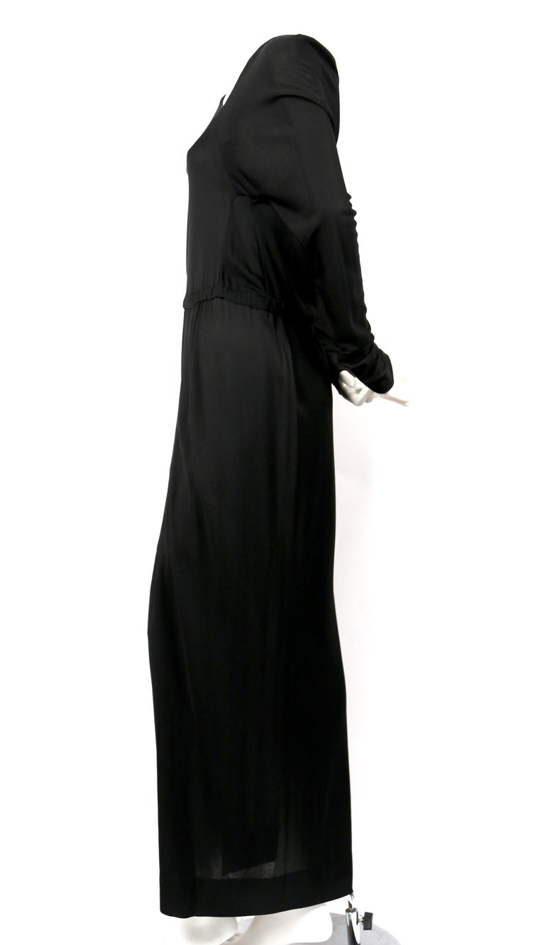 Jet-black, silk jersey gown with asymmetrical cut designed by Halston dating to the 1970's. No size is indicated however this would best fit a US 4-6. Approximate measurements: bust 33-34