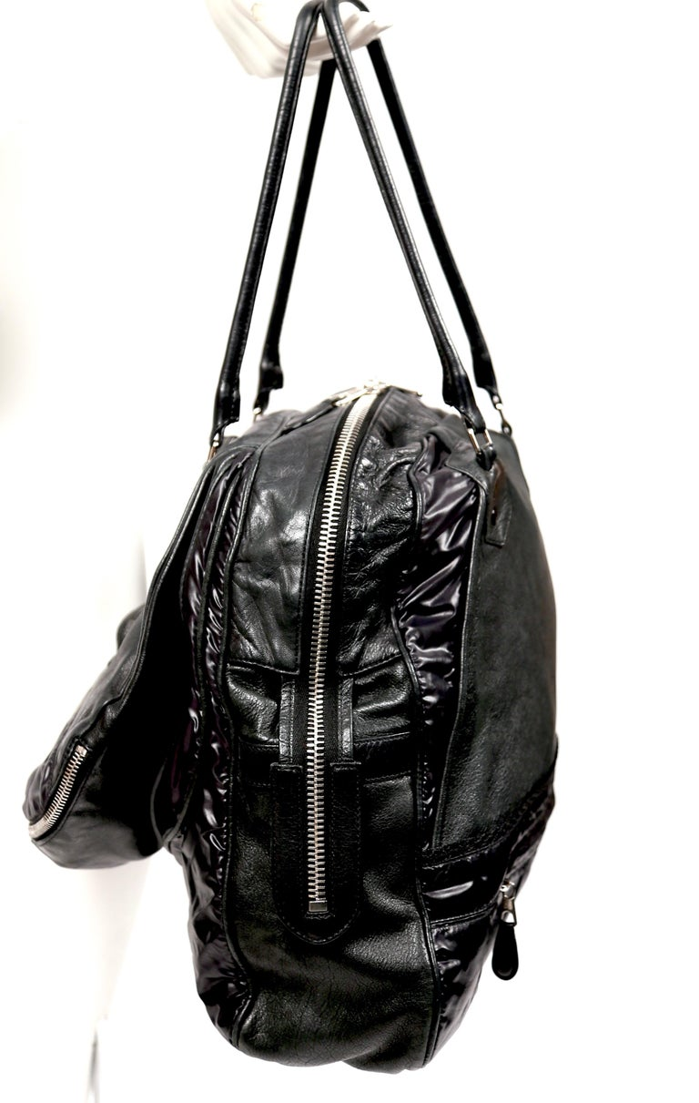 Very rare, black parachute bag with chevre leather and nylon insets designed by Nicolas Ghesquiere for Balenciaga dating to 2003. Bag features silver-toned hardware, two rolled shoulder straps, single exterior compartment with interior zip pocket,