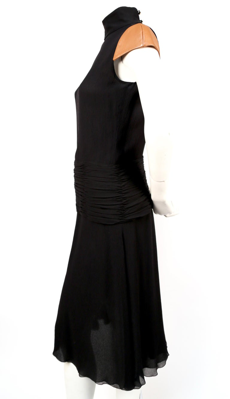 Black, silk-crepe dress with open back, high neck and leather cap sleeves from Gianni Versace Couture dating to 2001, exactly as seen on the runway. Labeled a size 40. Best fits a US 4. Fully lined. Hidden zipper at lower back and three buttons at