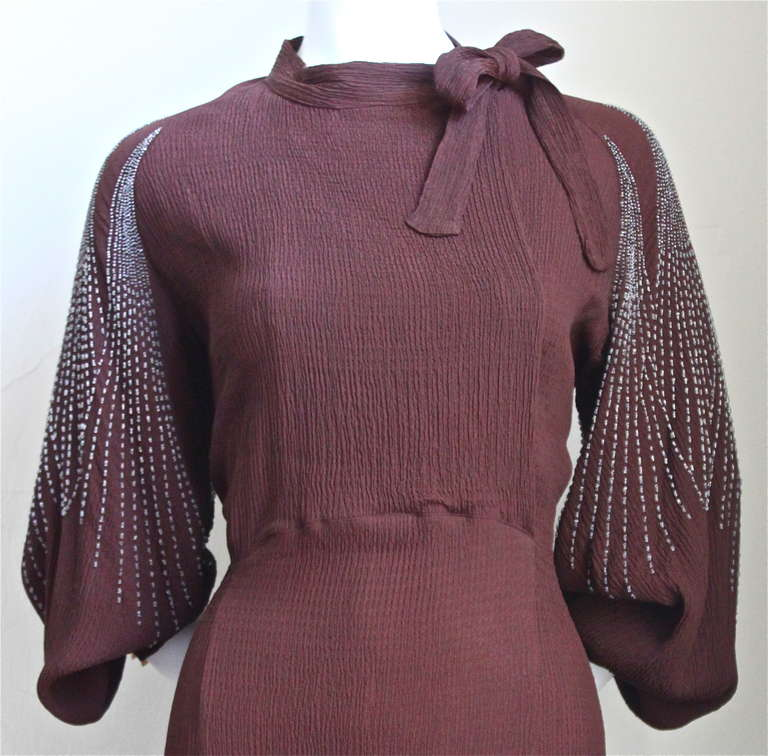 Rich brown crepe dress with heavily beaded sleeves from Mainbocher dating to the late 1930's. Fits a US size 8-10. Dress measures approximately:  40