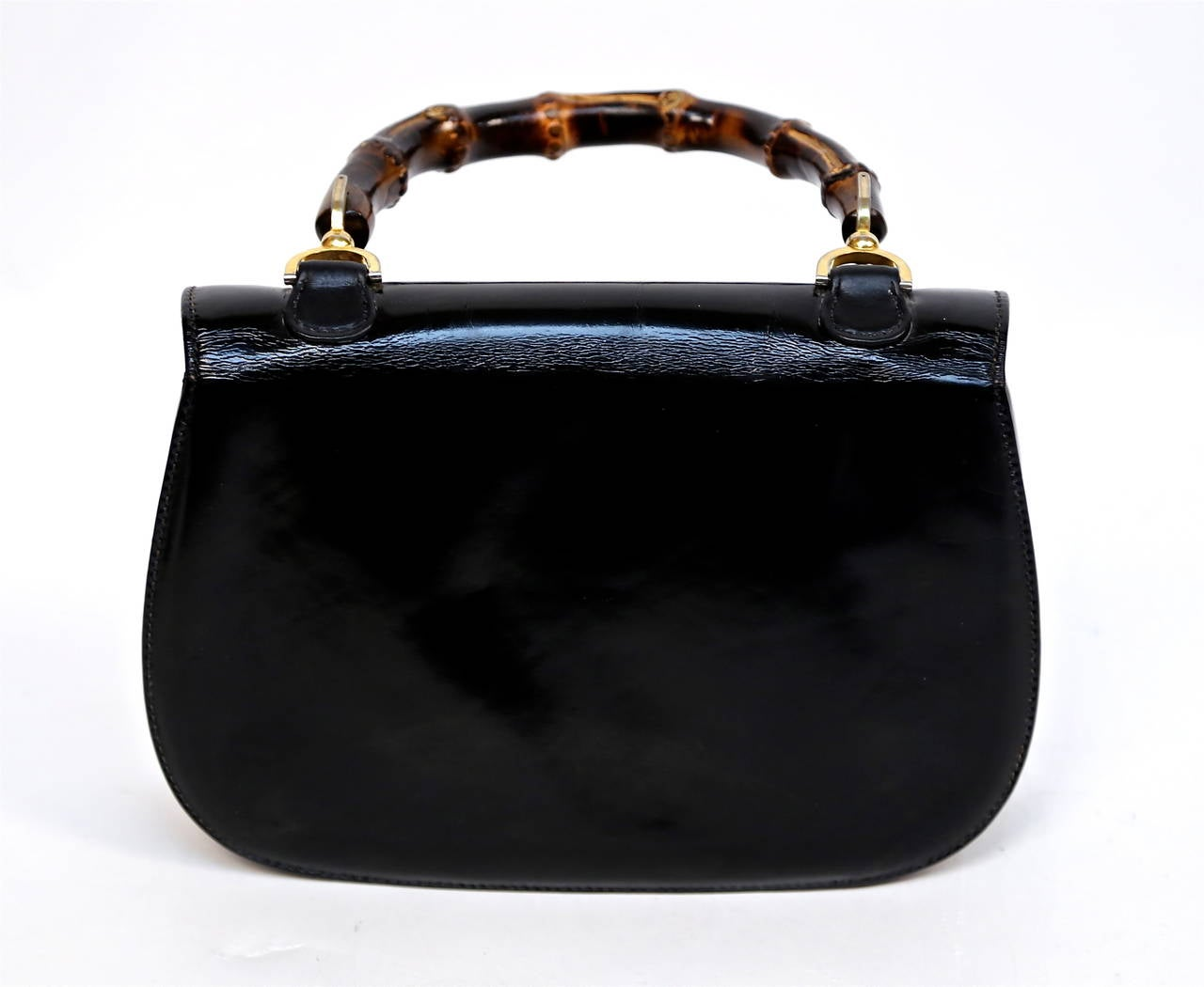 """Jet black patent leather bag with brown bamboo and brass handle designed by Gucci dating to 1975. Bag measures approximately 10.5"""" wide by 7"""" tall by 3"""" deep. Handle has a 4.5"""" drop. Bag had one large compartment and one slot packet. Made in Italy."""