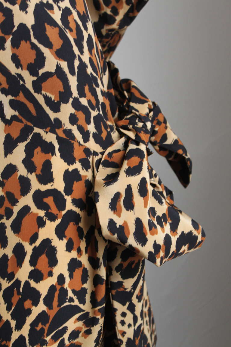"Leopard printed silk dress with asymmetrical side tie from Yves Saint Laurent dating to Fall 1986. Labeled a French size 38. Approximate measurements: shoulders 16"", bust 36"", waist 26"" hips 37"", arm length 23.25"" and overall length 42"".  Fits a US"