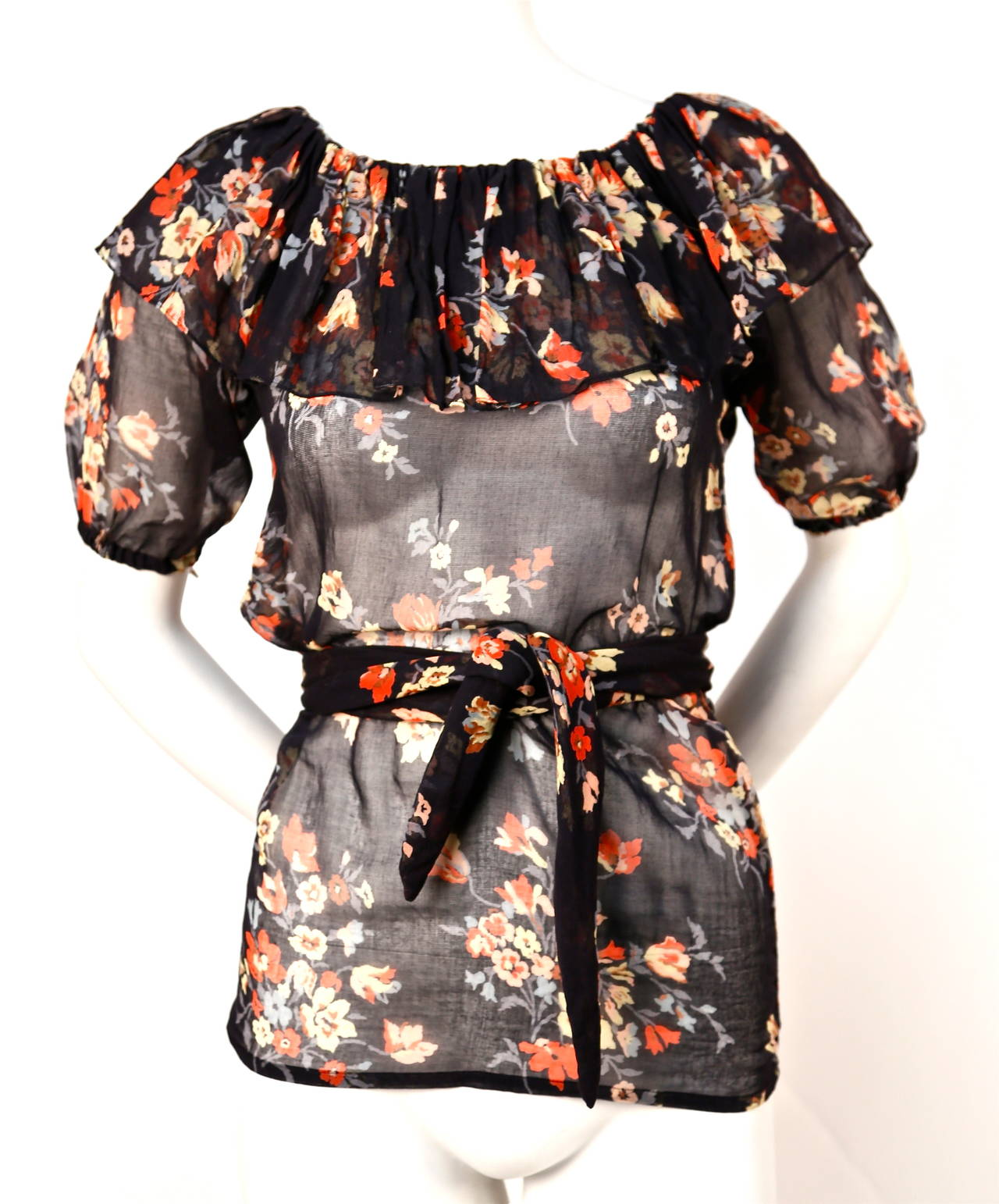 "Semi-sheer cotton floral blouse with flounced neckline and matching belt from Yves Saint Laurent dating to the 1970's. No size is indicated although this will best fit a size XS. Approximate measurements:  hem width 34"" and length 26"". Can be worn"