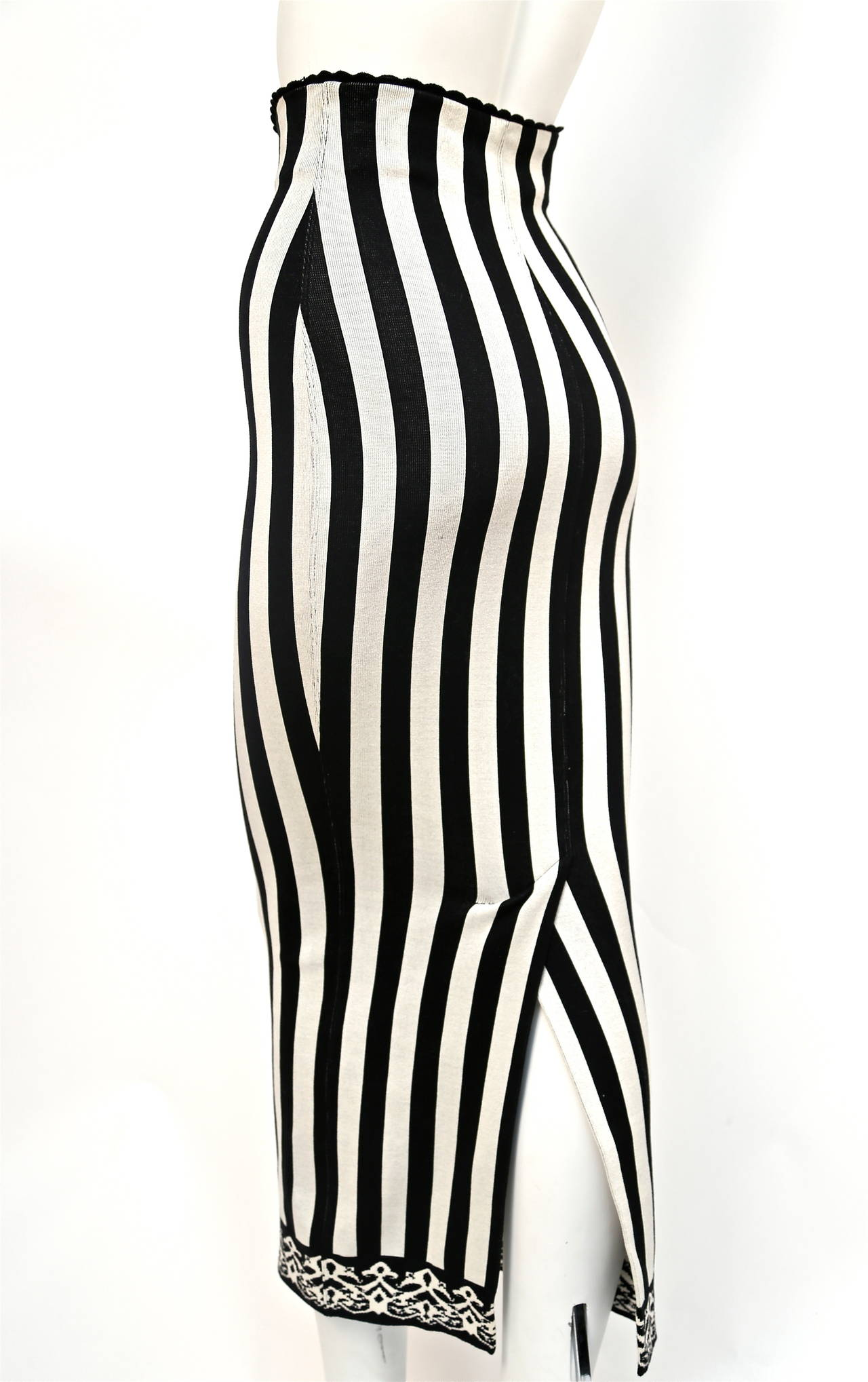 "Black and white striped skirt with scalloped waistline and trim at hemline from Azzedine Alaia dating to 1992. Size 'S'. Approximate measurements (unstretched): waist 23.5"", hips 30"" and length 36"". Pulls on. Made in Italy. Excellent condition."