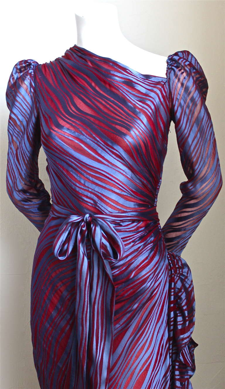 Very rare purple satin and sheer raspberry silk gown with side flounce, asymmetrical shoulder and long sash from Saint Laurent dating to the early 1970's. Dress is labeled a French size 40 however this dress is very small and best fits a US 2.