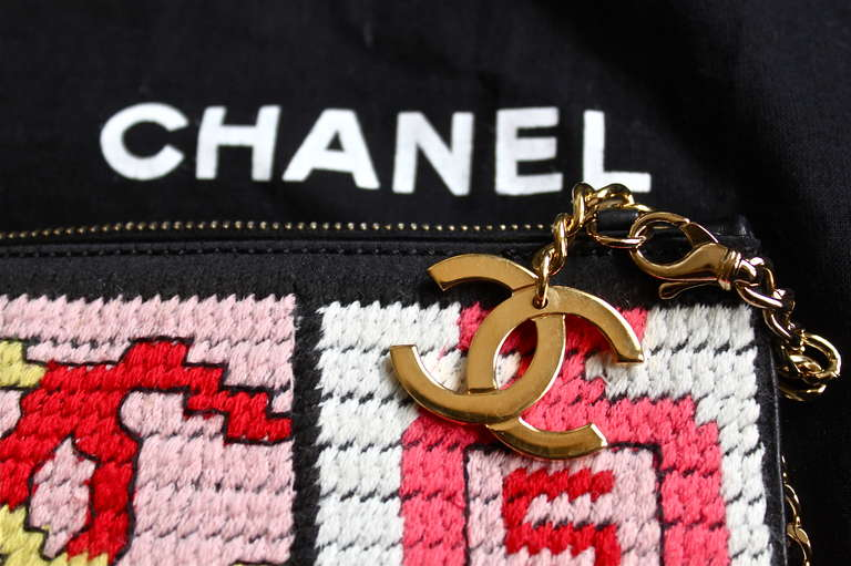 Needlepoint bag with lucky symbols motif from Chanel.  Symbols include: a bow, interlocking CC logo, Chanel No. 5 perfume bottle, a # 5, and a shamrock. Great as an evening bag. Bag measures approximately 8.5