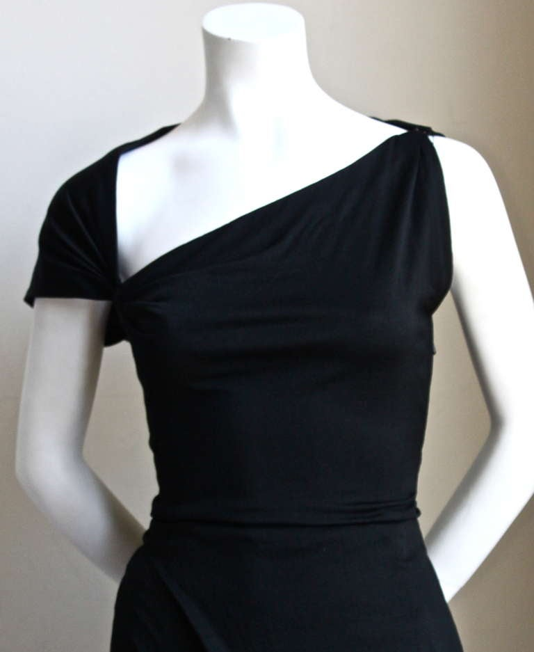 "Very rare, jet black, wool jersey haute couture dress with asymmetrical cut and draping from Pedro Rodriguez dating to the 1950's. Best fits a US 2. Approximate measurements: bust 32"", waist 23-24"" and length 42"". Made in Spain. Side zip entry."