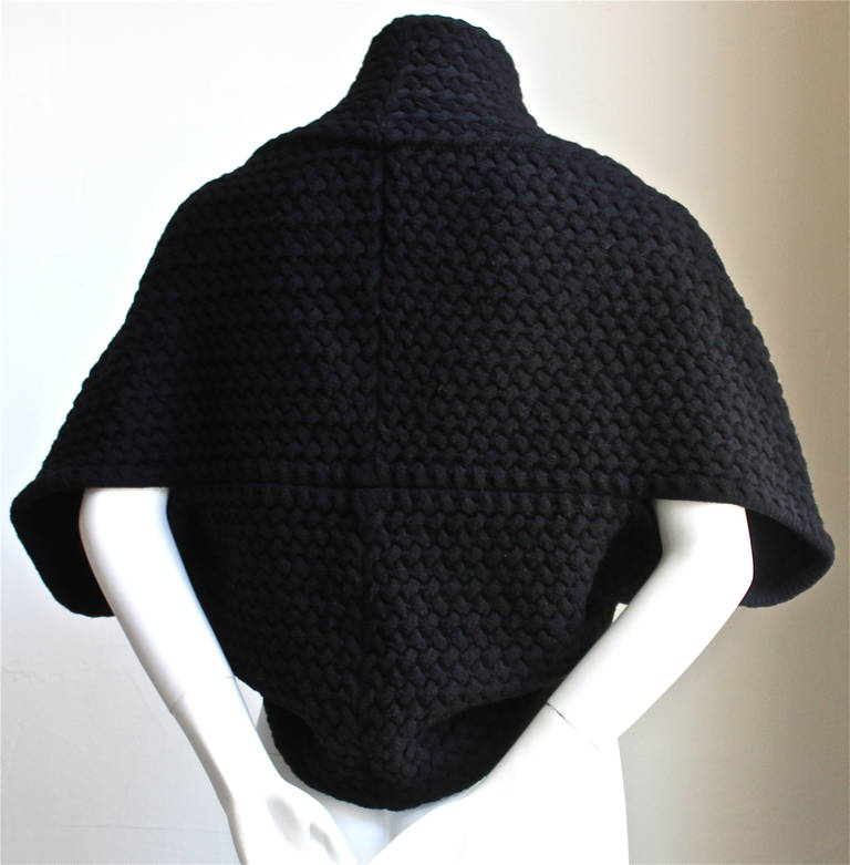Jet black basket weave shrug designed by Azzedine Alaia. Labeled an size XS. Hidden button closure. Very soft and stretchy material. 74% wool and 26% ply. Made in Italy. Excellent condition.