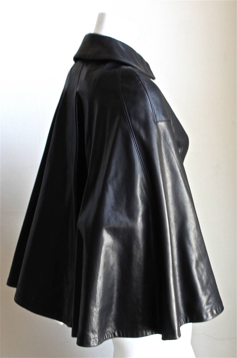 "Very unusual, jet black leather cape jacket from Junya Watanabe for Comme Des Garcons exactly as seen on the runway for fall of 2011. Labeled a size XS, which best fits a US 2 (up to 32"" bust and 27"" waist). Zips up with heavy duty silver toned"