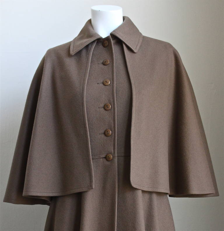 Dark taupe brown fitted long coat with capelet from Yves Saint Laurent dating to the 1970. Exact version as seen on Francoise Hardy. Labeled a French size 38 however this coat is quite small and better suits a FR 36. Approximate measurements: