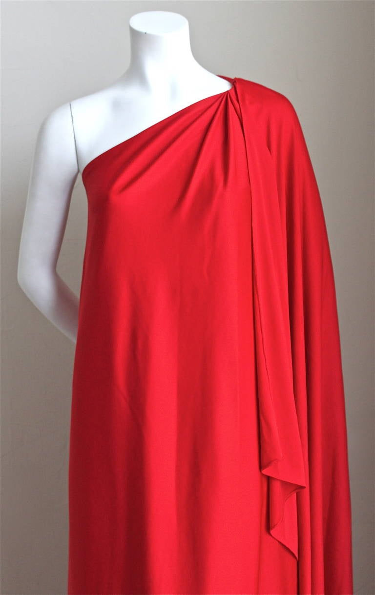 "Vivid red jersey Grecian gown with draping at shoulder from Halston IV dating to the 1970's. Dress is labeled a 'S' although it fits an XS-M due to loose shape. Approximate measurements: bust 34-36"" max, hips 38"" max and length 59"". Made in the U.S."