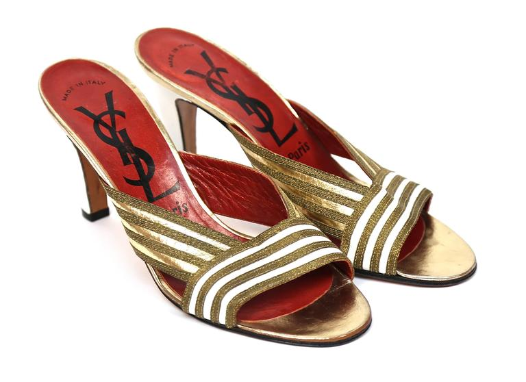 """Unworn gold and white leather heels from Yves Saint Laurent dating to the late 1970's. Size. 6.5. Insoles measure approximately 9.5"""" long by 3"""" wide. Heels are approximately 3.5"""" tall. Made in Italy. Excellent/unworn condition."""