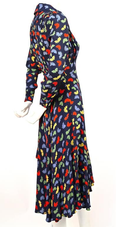 Very rare Ossie Clark dress from Quorum dating to the 1970's. Celia Birtwell fan printed fabric. Plunging neckline. Zips up side. Adjustable ties at back. Colors are blue, red, yellow, and green. Covered buttons at wrists. Labeled a UK size 8 which