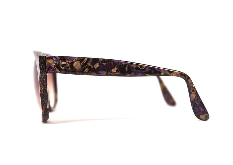 Vivid purple and gold mosaic sunglasses with gilt EK logo at temples from Emmanuelle Khanh dating to the late 1970's. Oversized frames are great fort a medium or larger sized face. Approximate measurements: 155 mm from temple to temple, 58 mm from