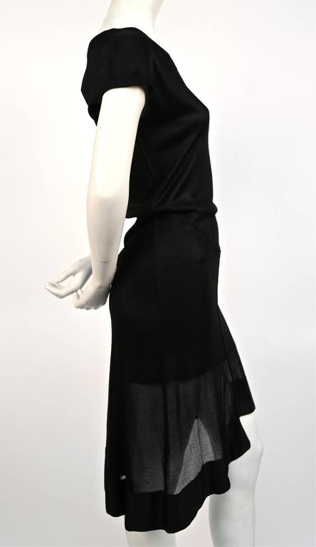 Jet black viscose dress with sheer asymmetrical hemline from Azzedine Alaia dating to spring of 1992. Labeled a size 'M', although this will also fit a size S. Approximate measurements: 33-34