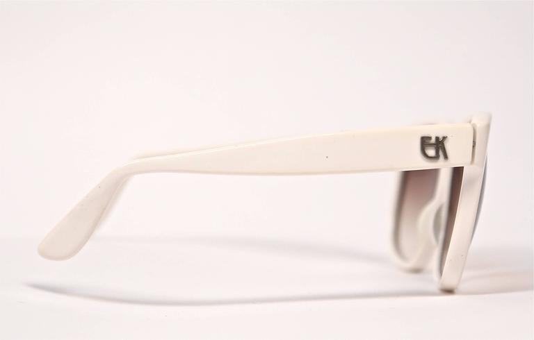 Oversized white plastic sunglasses with metal EK logo at temples from Emmanuelle Khanh dating to the 1980's. Great fort a medium or larger sized face. Approximate measurements: 155 mm from temple to temple, 58 mm from top to bottom and arm length is