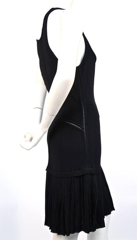 Black knit dress with drop waist and pleated skirt from Azzedine Alaia dating to the 1990's. Labeled a size 'M'. Approximate un-stretched measurements laying flat: bust 33-34