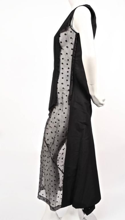 "Very rare black paneled dress with sheer black dotted tulle inserts and fishtail hemline from Comme Des Garcons dating to fall of 1997 as seen on the runway. Size 'M'. Approximate measurements: bust 34.5"", waist 29.5"", hips 37"" and"
