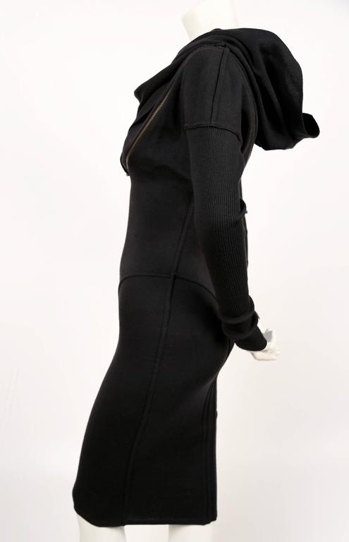 Iconic black wool seamed zipper dress with hood designed by Azzedine Alaia dating to fall of 1986. Well documented piece. Very flattering seams with spiral zipper that cleverly follows the contours of dress seams. 'Hood' can be draped for a more