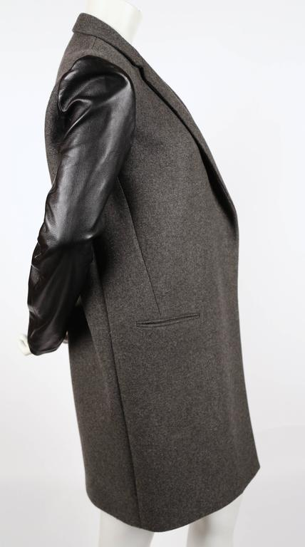 "Charcoal grey crombie coat with black lambskin leather sleeves designed by Phoebe Philo for Celine. Labeled a French size 36 which best fits a size XS or S. Approximate measurements: shoulder 15.5"" , shoulder seam to under arm 8"", bust 38"", hips"