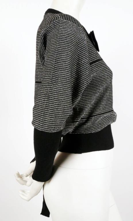 """Black and silver lurex striped sweater with satin bowtie designed by Sonia Rykiel dating to the 1970's. Labeled a French size 36. Approximate unstretched measurements: shoulder 17"""", bust 36"""", waist 24"""" (with tie to tighten), arm length 22"""" and"""