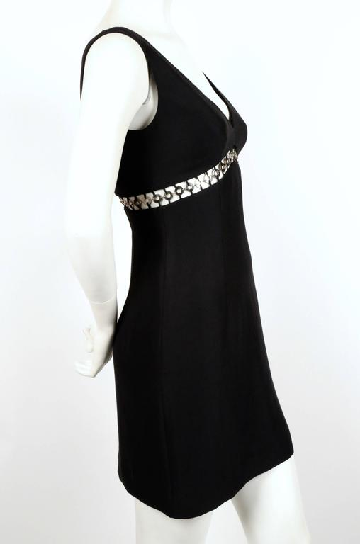 Jet black mini dress with cut out and silver metallic rings from Sophie Sitbon dating to the 1990's. Best fits a US 2. Approximate measurements: bust 32