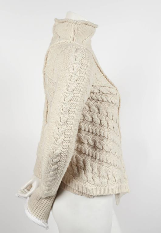 """Very rare cream cable knit sweater with asymmetrical hemline designed by Phoebe Philo for Celine dating to Fall of 2011. Labeled a size 'S'. Fits a size extra-small or small. Approximate measurements (unstretched): shoulder 14"""", bust"""