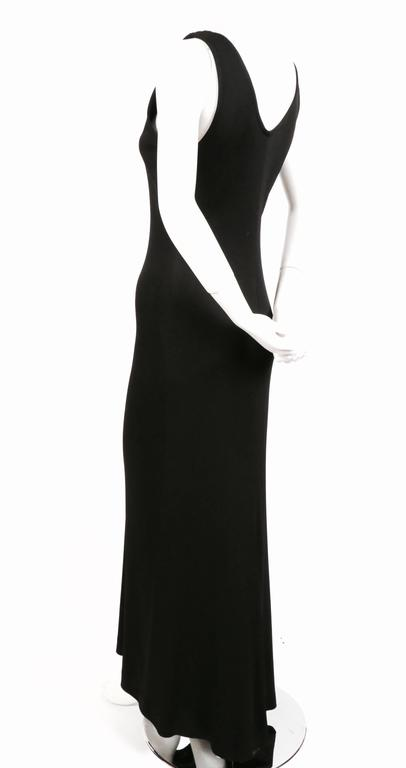 """Jet black, jersey dress with unique sweet train hemline in back from Yves Saint Laurent dating to 1986. Labeled a French Size 38. Approximate measurements (unstretched): bust 32"""", waist 28"""", hips 34"""" and length in front 57"""" and"""