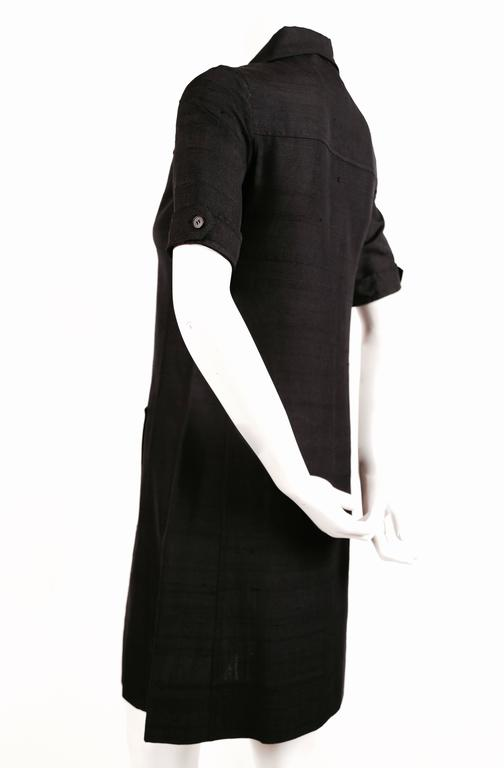 "Jet black raw silk safari dress from Yves Saint Laurent dating to the 1960's. Labeled a size 34 which best fits a size 2 or 4. Approximate measurements: 14"" shoulders, 32-33"" bust, 37"" hips, 10"" arm length from shoulder and 35"" overall in length."