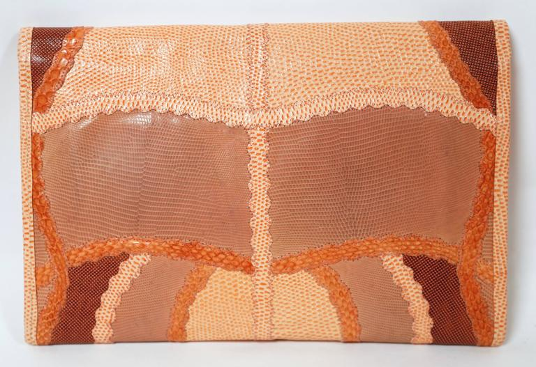 "Vivid peach patchwork clutch made of reptile skins from Carlos Falchi. Cleverly pieced so that pattern symmetrically matches on body of bag and flap. Bag measures approximately 12"" wide by 8"" tall. One large compartment with a slot pocket. Made in"