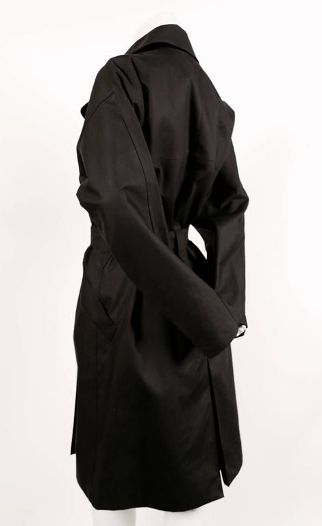 "Classic soft black cotton trench designed by Azzedine Alaia. French size 40. Coat has a loose fit with fitted belt. Approximate length 42"". Black buttons. Silver buckle at waist. Pockets at hips. Excellent condition."