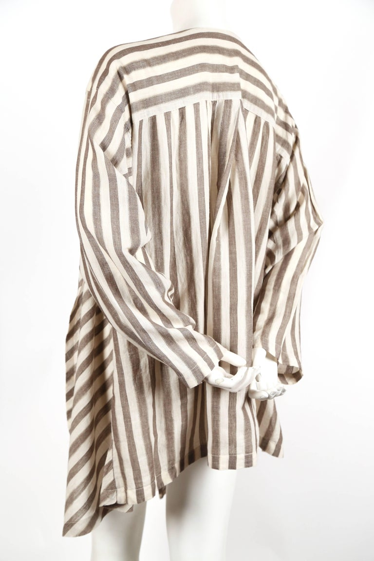 Very lightweight striped cotton jacket with asymmetrical cut designed by Issey Miyake dating to the early 1980's. No size is indicated however this will fit many sizes due to the oversized cut. Open closure. Very good condition.